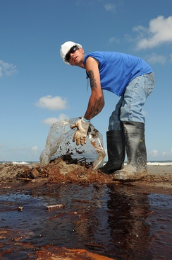 A worker cleans up oily waste on Elmer's Island just west of Grand Isle, La., 21 May 2010
