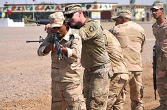 A trainer with Company A, 1st Battalion 502nd Infantry Regiment, Task Force Strike, 101st Airborne Division assists Iraqi army ranger students during a room clearing drill at Camp Taji, Iraq on 18 July 2016