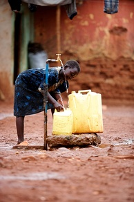 A young girl collects clean water from a communal water supply in Kawempe, Uganda.