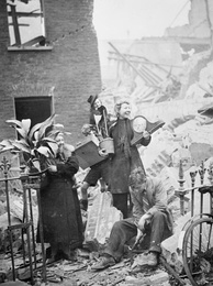 Women salvaging possessions from their bombed house, including plants and a clock