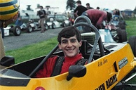 A man in his early twenties sitting in a stationary yellow racing car