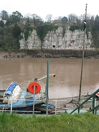 Limestone cliffs seen from the riverside at Chepstow, showing Gloucester Hole, an enlarged natural opening