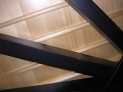 This view of the underside of a 182 cm (6-foot) grand piano shows, in order of distance from viewer: softwood braces, tapered soundboard ribs, soundboard. The metal rod at lower right is a humidity control device.