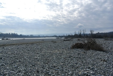 Photo shows a river bordered by an immense bed of white stones. There are mountains in the distance.