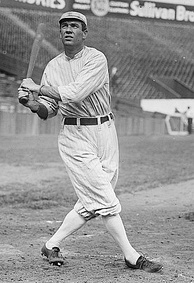A black and white photograph of a man swinging a baseball bat.