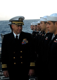 "A navy officer wearing Service Dress Blues, inspects enlisted sailors in their service dress blue ""crackerjacks"" in February 2008."