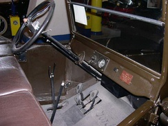 In the Ford Model T the left-side hand lever sets the rear wheel parking brakes and puts the transmission in neutral. The lever to the right controls the throttle. The lever on the left of the steering column is for ignition timing. The left foot pedal changes the two forward gears while the centre pedal controls reverse. The right pedal is the brake.
