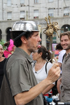 Pastafarian protester wears a colander while showing an icon of the Flying Spaghetti Monster