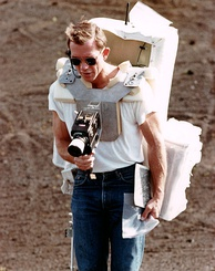 Man around age 40 with sunglasses and a large backpack takes a photograph with a camera mounted on his chest