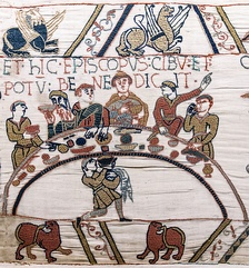 "ET HIC EPISCOPUS CIBU(M) ET POTU(M) BENEDICIT (""And here  the bishop blesses the food and drink""). The feast at Hastings, after which a castle was ordered to be built, following which battle was joined. Roger de Beaumont is possibly depicted as the bearded figure, see detail above. Bayeux Tapestry"