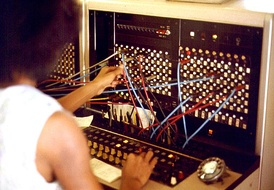 A telephone operator manually connecting calls with cord pairs at a telephone switchboard.