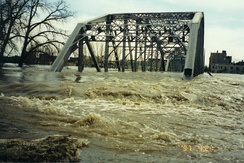 Dirty flood water rushing through the roadway of a bridge.