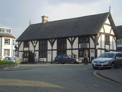 A half timbered building of two floors, with four sets of leaded windows to the front aspect and one set to the side. The build has a steep, slate roof, with a single chimney placed left of centre. Steps and a ramp lead up to its single visible entrance