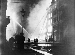 Firefighters at work amongst burning buildings, during the large raid of 10/11 May