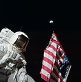 Harrison Schmitt poses with the American flag and Earth in the background during Apollo 17's first EVA. Eugene Cernan is visible reflected in Schmitt's helmet visor