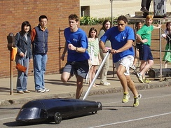 Two pushers exchange the buggy for Kappa Delta Rho on the first hill of Sweepstakes.