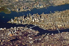 View of New York City from an airplane. Lower Manhattan is in the center of the image, Brooklyn is across the East River below Manhattan, and above Manhattan across the Hudson River is Hudson County, New Jersey.