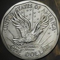 One side of a coin design, depicting an eagle flying above a mountaintop