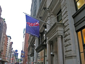 A Tisch School flag (with an older logo) displayed at the building's main entrance, c. 2007.