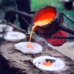 Liquid bronze, being poured into molds during casting.