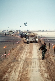 A column of M113 armored personnel carriers and other military vehicles of the Royal Saudi Land Force along a channel cleared of mines during Operation Desert Storm.