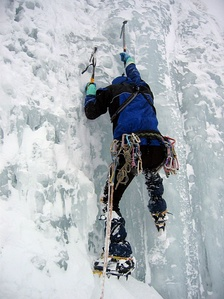 An ice climber using ice axes and crampons.