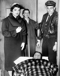 Kennedy lying on a gurney following spinal surgery, accompanied by Jackie, December 1954