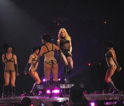 A blond female stands on a raised platform of a stage. Her wavy hair falls around her and she wears a black top and high boots while holding a microphone in her left hand. She is encircled by female dancers in short black hair and nude body suits which are lined in black. They appear to be hopping.
