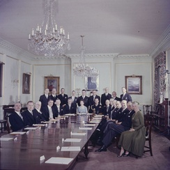 The first meeting of the Queen's Privy Council for Canada before the reigning sovereign; in the State Dining Room of Rideau Hall, Queen Elizabeth II is seated at centre, with Prince Philip, Duke of Edinburgh, to her left, and Prime Minister John Diefenbaker at her right; 14 October 1957