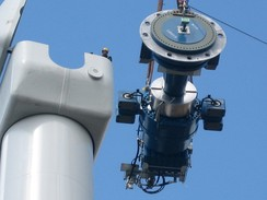 Components of a horizontal axis wind turbine (gearbox, rotor shaft and brake assembly) being lifted into position