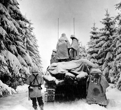 Men of the 504th Parachute Infantry Regiment advancing through a snow-covered forest during the Battle of the Bulge, December 1944