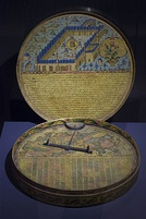 A historical compass decorated with illustrations and tables.