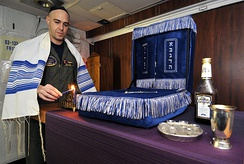 US serviceman lighting a Menorah in observance of the first day of Hanukkah
