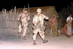 Soldiers of the 10th Mountain Division sweep a Somali village for weapons in 1993.