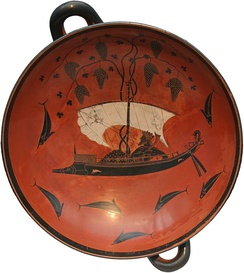 Cup with a coral red background by Exekias. Dionysus reclines on a ship which sprouts grapevines and is surrounded by dolphins, c. 530 BC. Dionysus cup: Staatliche Antikensammlungen, Munich