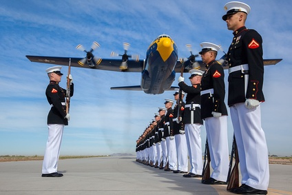 A U.S. Marine Corps C-130T Hercules aircraft with the Blue Angels, the Navy's flight demonstration squadron, flies over Marines with the Silent Drill Platoon at Marine Corps Air Station Yuma, Arizona.
