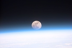 This view from orbit shows the full moon partially obscured by Earth's atmosphere.