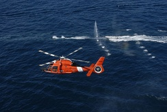 A demonstration of warning shots fired at a non-compliant boat by a USCG HITRON MH-65C and its M240 machine gun