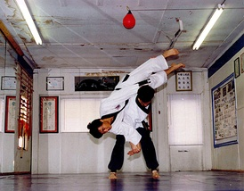 Hapkido students practice throws and joint manipulation in a dojang.