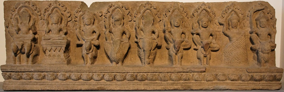 The nine Devas, Khleangs artwork from Cambodia (~1000 CE). From left to right: Surya (Sun) on chariot, Chandra (Moon) on pedestal, Shiva on bull, Varuna on crocodile, Indra on elephant, Kubera on horse, Agni on ram, Rahu on clouds and Ketu on lion.