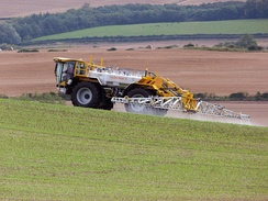 A Lite-Trac four-wheeled self-propelled crop sprayer spraying pesticide on a field