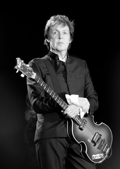A serious, standing man holding his guitar with his left hand and placing his other hand on his left arm