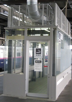 An enclosed smoking area in a Japanese train station. Notice the air vent on the roof.