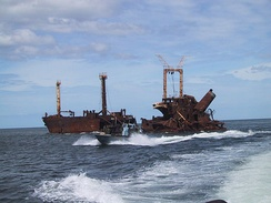 A LTTE Sea Tiger fast attack fiberglass boat passing a Sri Lankan freighter sunk by the Sea Tigers just north of the village of Mullaitivu, North-eastern Sri Lanka