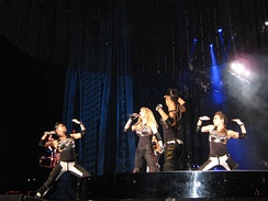 Left profile of a blond female in a tight black dress with gloves and wrist bands singing. A number of similarly dressed dancers encircle her while making gesture with their hand. Blue light is visible behind her and a metallic cover is present above their head.