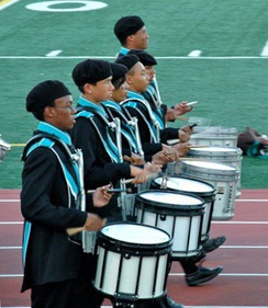 Snare drummers in a high school marching band playing with traditional grip