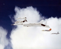 The second XB-70 Valkyrie prototype flying in a formation with F‑104 (plane with red tail, starboard of the XB‑70), 8 June 1966. Shortly after this photograph was taken the F‑104 and XB‑70 collided, killing the F‑104 pilot Joe Walker and the co‑pilot of the XB‑70.
