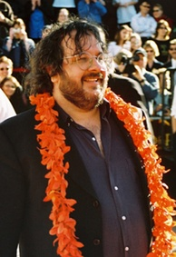 Peter Jackson looks away from the camera and has a garland over his neck.