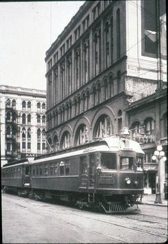 A train with two cars passing through a built-up downtown on tracks embedded in the street