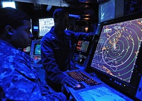 Military air traffic controller on US Navy aircraft carrier monitors aircraft on radar screen